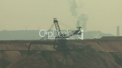 Open-cast mining. Defocus from filling up excavator. Power plant and wind engine in the background. Surface mine.