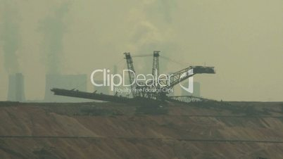 Open-cast mining. Defocus from excavator and power plant in the background. Surface mine.