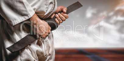 Composite image of fighter tightening karate belt