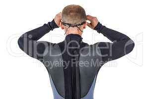 Rear view of swimmer in wetsuit wearing swimming goggles