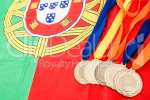 Close-up of gold medals on portuguese flag