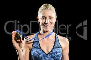 Female athlete posing with gold medal around his neck