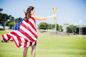 Female athlete wrapped in american flag holding fire torch
