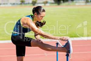 Female athlete warming up above hurdle