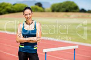 Portrait of female athlete standing beside hurdle