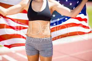 Mid section of female athlete holding up american flag on runnin