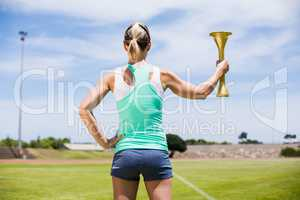 Rear view of female athlete holding a fire torch
