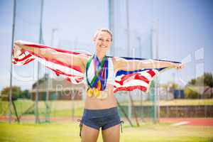 Portrait of female athlete holding up american flag with gold me