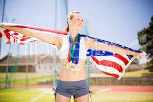 Female athlete holding up american flag with gold medal