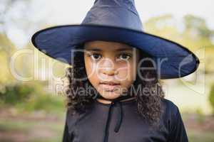 Portrait of cute girl dressing up as witch
