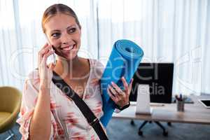 Casual business woman holding yoga mat
