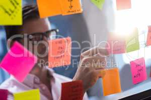 Hipster reading a post it on a window