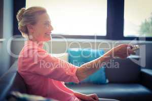 Senior woman changing tv channel