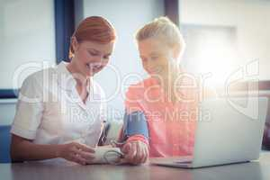 Female nurse checking blood pressure of senior woman