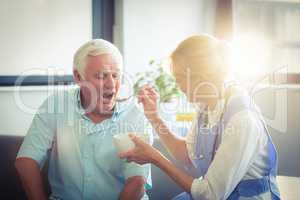 Female doctor feeding senior man