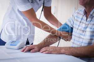 Mid-section of female doctor checking blood pressure of senior man