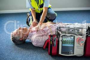 Paramedic using an external defibrillator on an unconscious patient