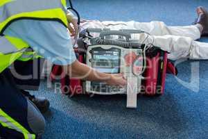 Paramedic using an external defibrillator during cardiopulmonary resuscitation
