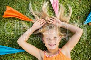 Young girl lying on grass around paper planes