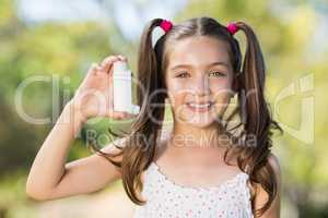 Girl holding an asthma inhaler in the park