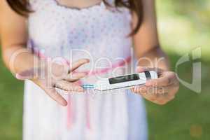 Girl testing diabetes on glucose meter