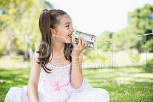Young girl speaking through tin can phone