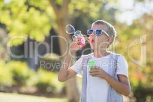 Young boy blowing bubbles through bubble wand