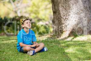 Young boy wearing a crown and sitting on grass