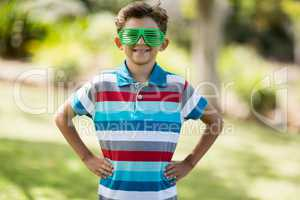 Young boy in shutter shades standing with hand on hip