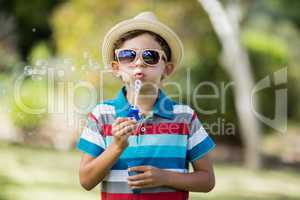 Young boy in sunglasses blowing bubbles through bubble wand