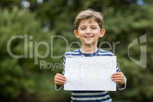 Boy in park holding placard that reads alphabets