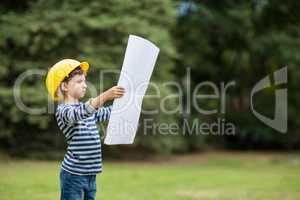 Boy in hard hat reading a plan