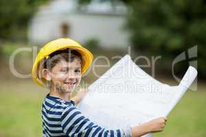 Boy in hard hat holding a plan