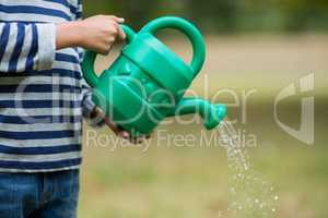 Boy pouring water from watering can
