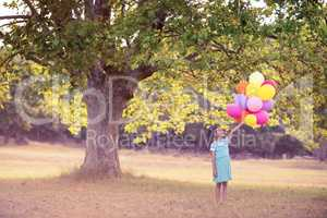 Girl holding a balloon in park