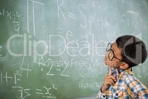 Thoughtful schoolboy looking at mathematical problem in classroom