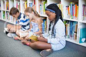 School kids sitting on floor and reading book in library