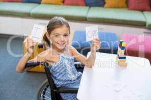 Disabled girl holding placard that reads I Can in library
