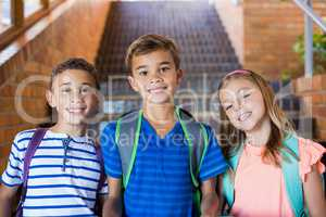 Portrait of smiling school kids standing together on staircase