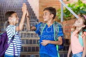 School kids giving high five on staircase