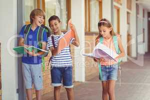 School kids reading books while walking in corridor