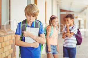 School friends bullying a sad boy in corridor
