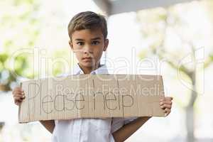 Schoolboy holding placard which reads please help
