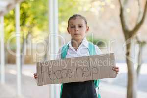Schoolgirl holding placard which reads please help