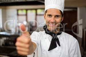 Portrait of smiling chef showing thumbs up