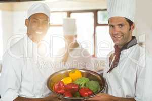Portrait of two smiling chefs holding a bowl of vegetable