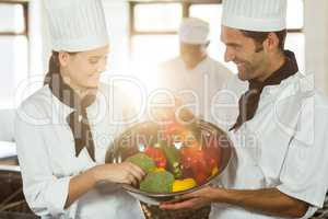 Two smiling chefs holding a bowl of vegetable