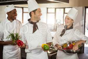 Smiling three chefs holding a vegetables