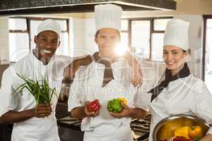 Portrait of three chefs holding a vegetables