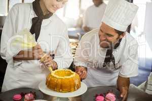 Two chefs preparing a cake